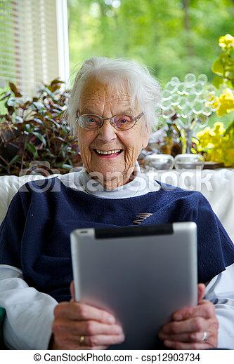 Happy Elderly woman using a tablet - csp12903734