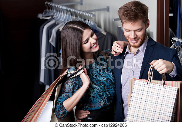 Attractive woman and young man go shopping at the store
