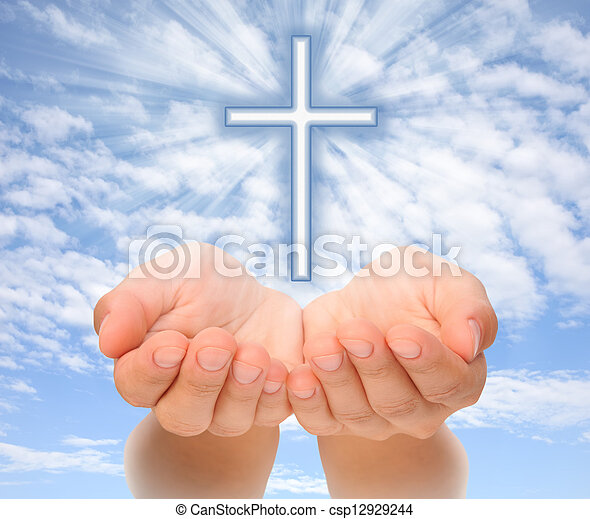 Hands holding Christian cross with light beams over sky - csp12929244