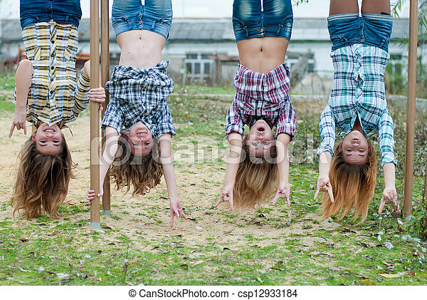 Four young girls hanging upside down in park - csp12933184