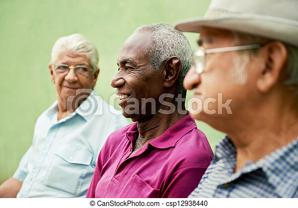 Group of old black and caucasian men talking in park - csp12938440