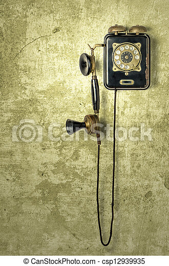 antique telephone on a grungy yellow wall - csp12939935