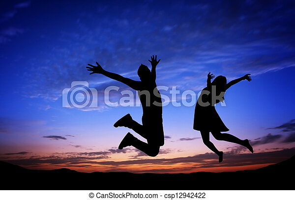 Silhouettes of couple jumping on sunset background - csp12942422