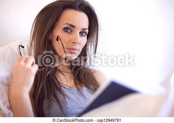 Young Adult Woman on her Bed Reading a Book - csp12949791