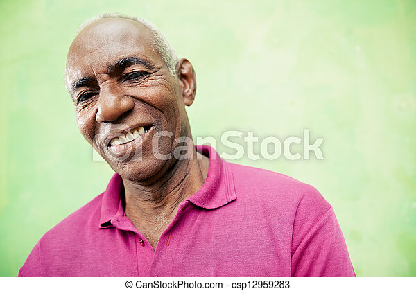 Portrait of elderly black man looking and smiling at camera - csp12959283