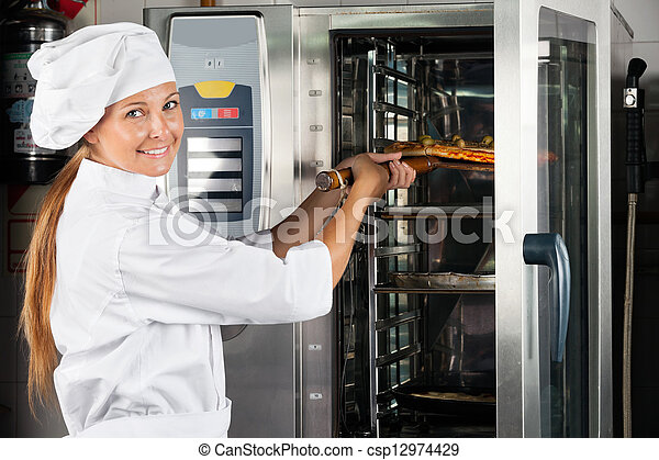 Chef Placing Pizza In Oven - csp12974429