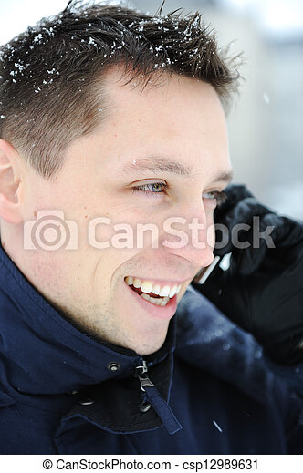 Young male adult speaking on phone at winter snow time - csp12989631