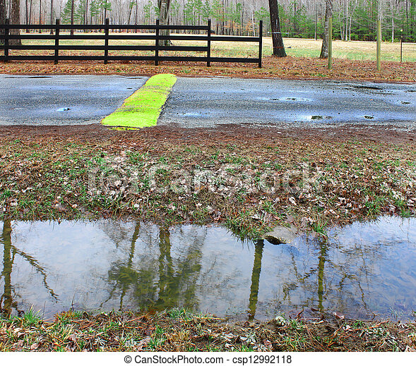 A ditch full of water runoff running along a road and fence with a speed bump and pothole in a rural neighborhood - csp12992118