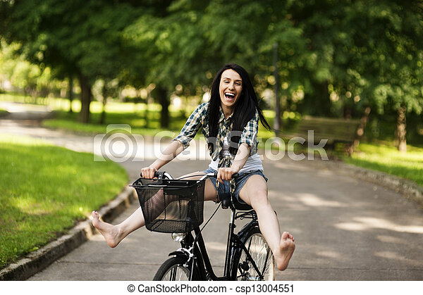 Happy young woman cycling through the park - csp13004551