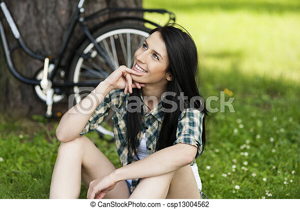 Happy young woman resting in park - csp13004562