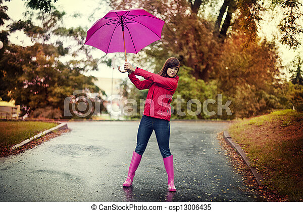 Young woman holding pink umbrella in a park - csp13006435