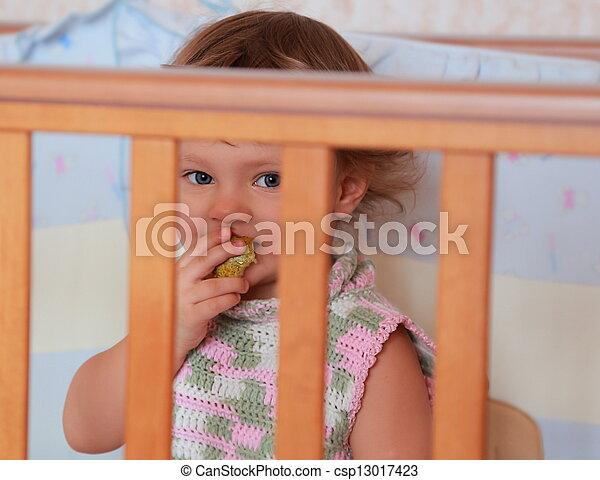 Baby girl eating fruit sitting in bed and funny looking blue eyes. Closeup portrait