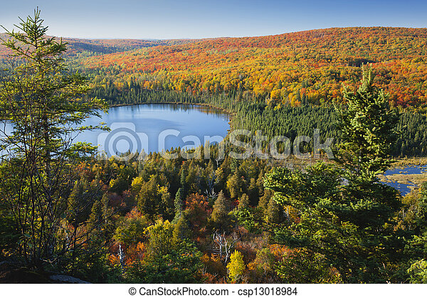 Small blue lake amid hills in autumn color - csp13018984