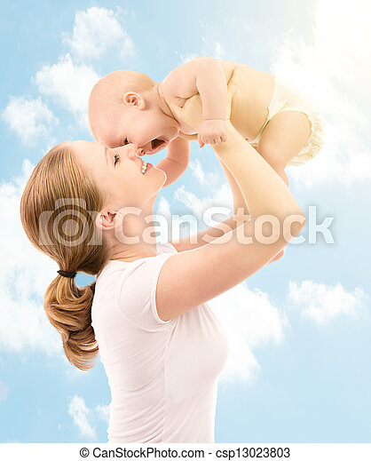 happy family. Mother kissing baby in the sky - csp13023803
