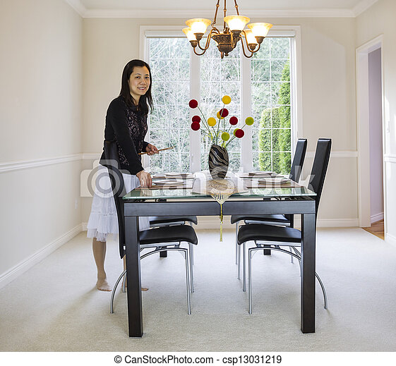 photo of mature woman placing bamboo chopsticks on place mats in family formal dining room with daylight coming through large windows in background - csp13031219