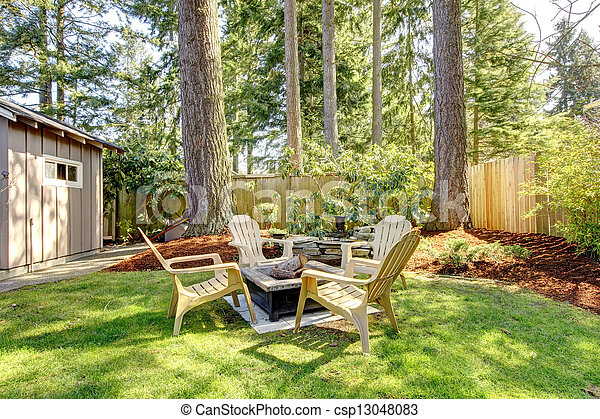 Home exterior Backyard with chairs and pine trees. - csp13048083