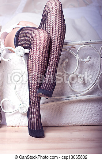 Beautiful female legs in fishnet stockings - csp13065802