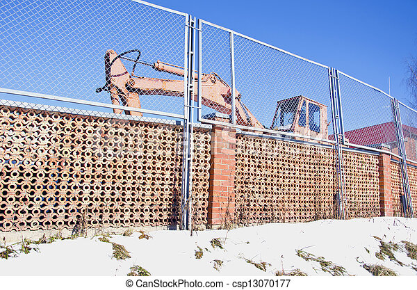 industrial place fence and old excavator machine - csp13070177