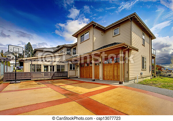 Large New luxury home exterior with orange and red driveway. - csp13077723