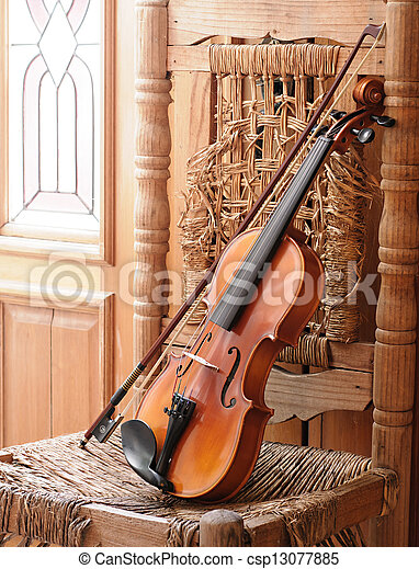 Violin lying on an old and ruined chair - csp13077885