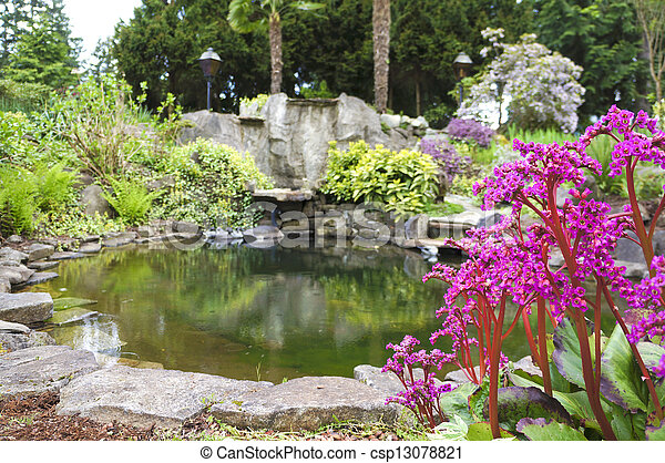 Spring American Northwest home water pond, large rock with landscape garden . - csp13078821
