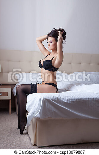 Sexy woman in black lingerie sitting on bed - csp13079887