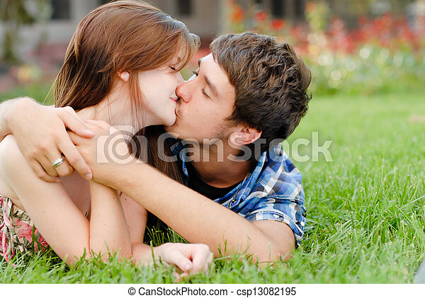 Young happy couple man and woman lying on green lawn and kissing - csp13082195