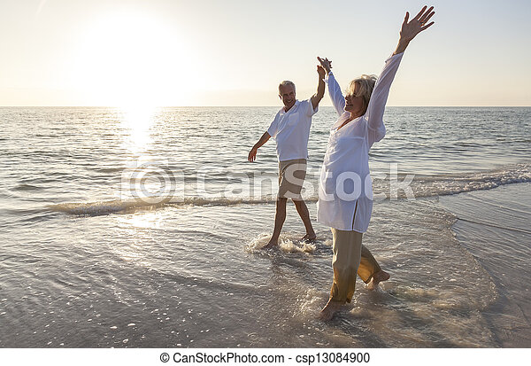 Happy Senior Couple Holding Hands Sunset Sunrise Beach - csp13084900