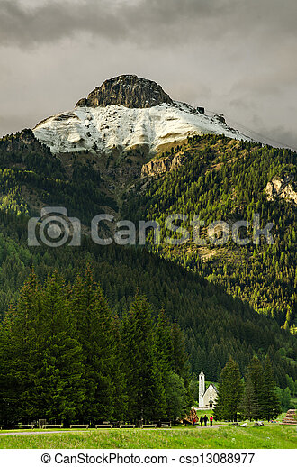 a view of a church with three people walking in atalian alps covered with some snow - csp13088977