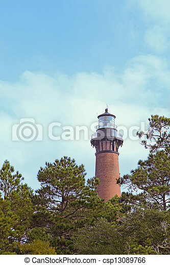 The red brick structure of the Currituck Beach Lighthouse rises over pine trees at Currituck Heritage Park near Corolla, North Carolina - csp13089766