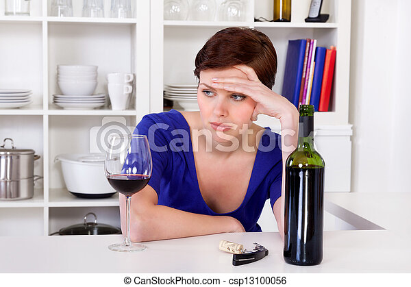 young sad thinkful woman drinking a glass of red wine - csp13100056