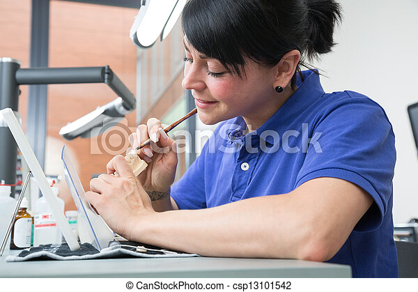 Technician in a dental laboratory applying ceramics to a prosthesis - csp13101542