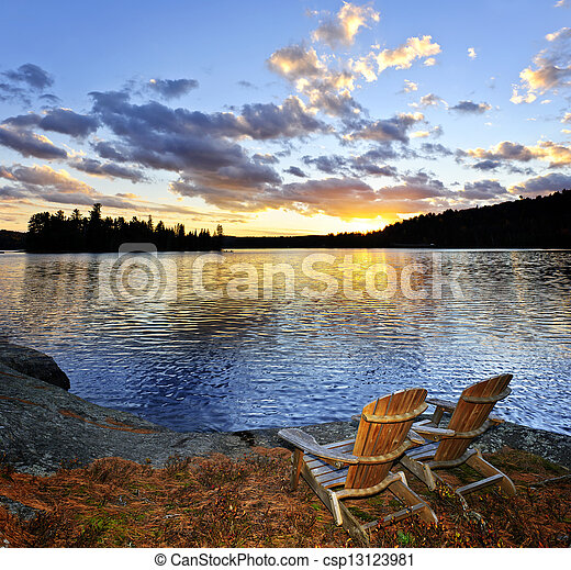 Wooden chairs at sunset on beach - csp13123981