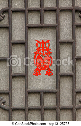 Chinese paper cut works on ancient traditional window lattice, in a rural courtyard, china