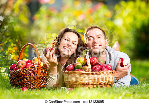 Couple Relaxing on the Grass and Eating Apples in Autumn Garden  - csp13133095