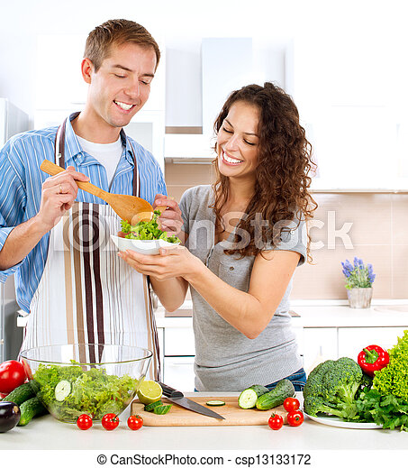 Young Man Cooking. Happy Couple Eating Fresh Vegetable Salad  - csp13133172