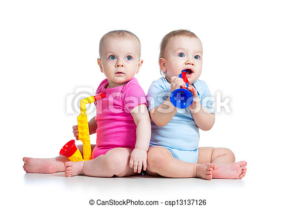 Funny babies girl and boy  playing musical toys. Isolated on white background - csp13137126