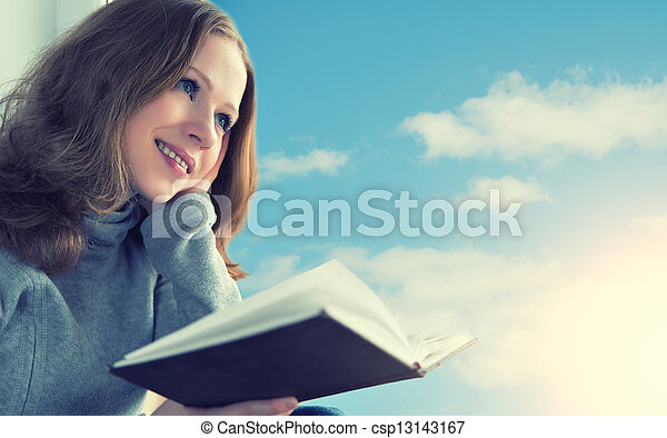 beautiful young woman reading a book while sitting at a window in the sky and sunset - csp13143167