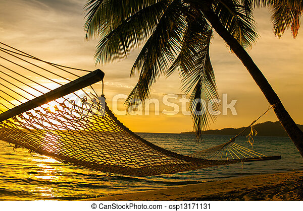 Hammock silhouette with palm trees on a beach at sunset - csp13171131