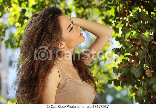 Long Healthy Hair. Young beautiful woman outdoors portrait. Soft sunny colors.