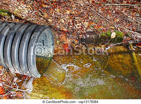 A waste water drainage pipe re-routing the water flow and polluting the environment at the same time  - csp13178384
