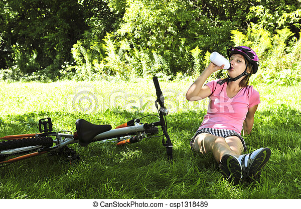 Teenage girl resting in a park with a bicycle - csp1318489