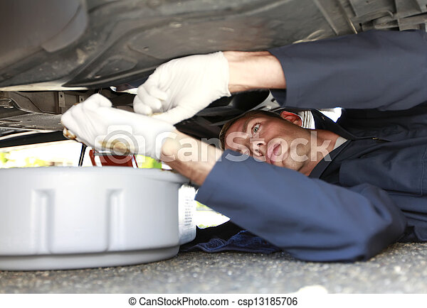 Man changing car oil laying under vehicle. - csp13185706