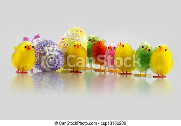 Coloured Easter chick and two eggs decorated in a light grey background - csp13186200