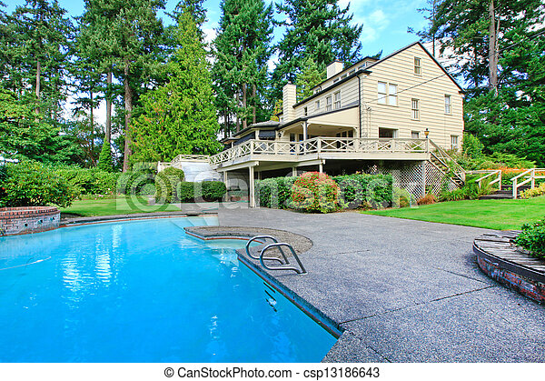 Large brown house exterior with summer garden and swimming pool - csp13186643