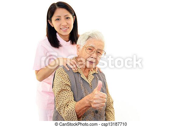 Friendly nurse with elderly woman - csp13187710