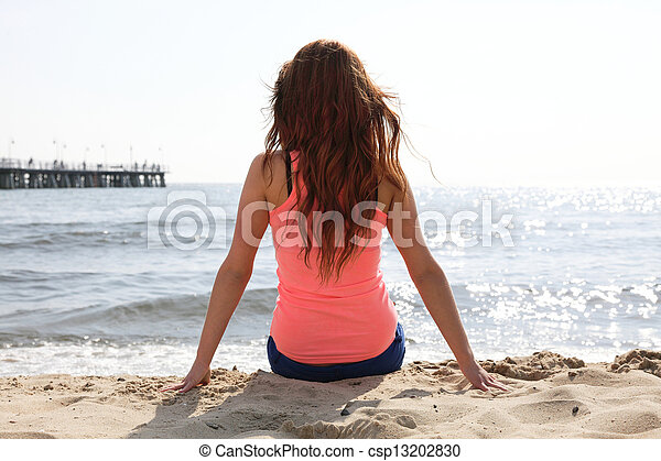 Beach holidays woman enjoying summer sun sitting in sand looking happy at copy space. Beautiful young model - csp13202830