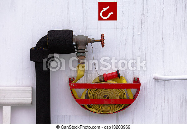 Fire hose on water outlet ready for fire emergency - csp13203969