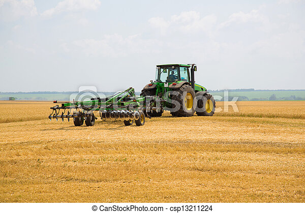 Tractor with cultivator in a field - csp13211224