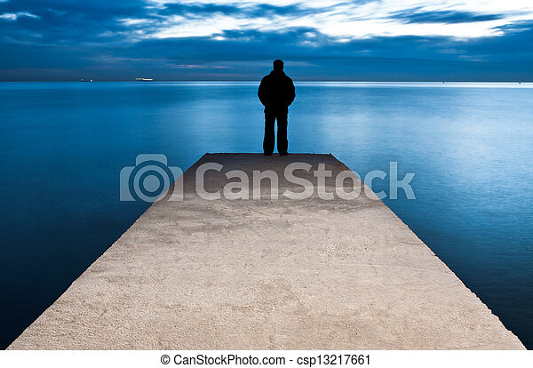 Man is standing on a jetty looking the sunset - csp13217661